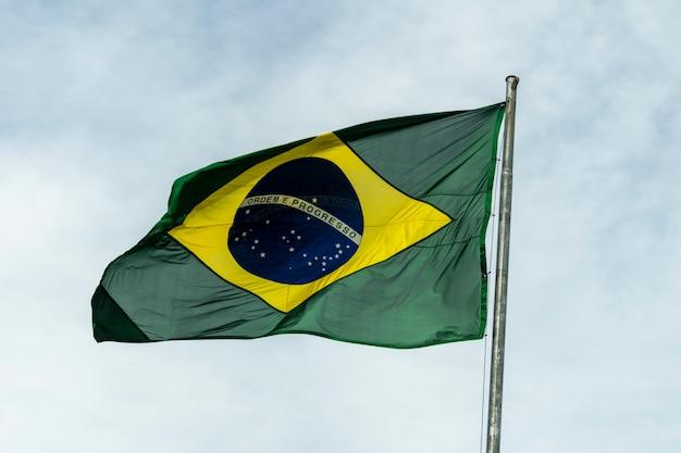 Drapeau du brésil flottant dans le ciel nuageux. ordre et progrès. drapeau brésilien