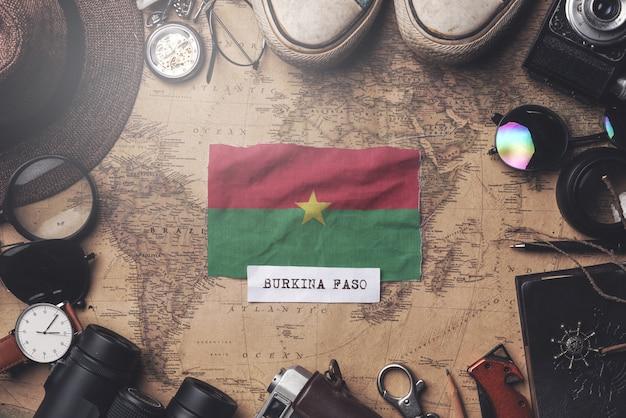 Drapeau du burkina faso entre les accessoires du voyageur sur l'ancienne carte vintage. tir aérien