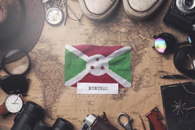 Drapeau du burundi entre les accessoires du voyageur sur l'ancienne carte vintage. tir aérien