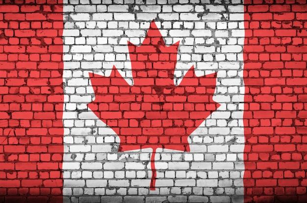 Le drapeau du canada est peint sur un vieux mur de briques