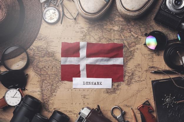 Drapeau du danemark entre les accessoires du voyageur sur l'ancienne carte vintage. tir aérien