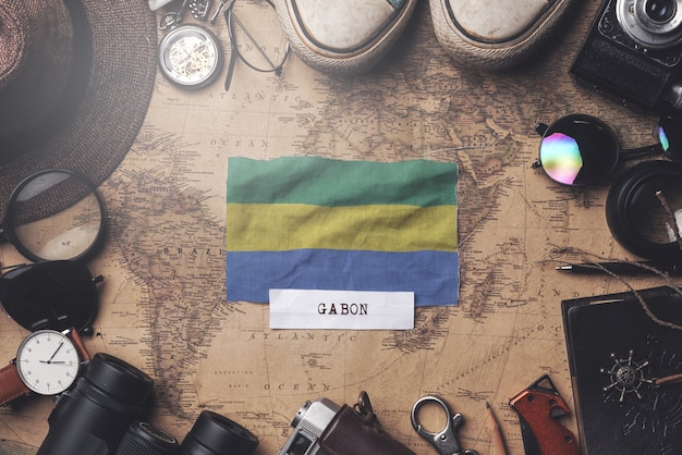 Drapeau du gabon entre les accessoires du voyageur sur l'ancienne carte vintage. tir aérien