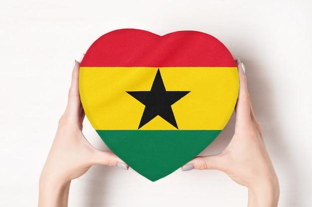 Drapeau du ghana sur une boîte en forme de coeur dans une main féminine