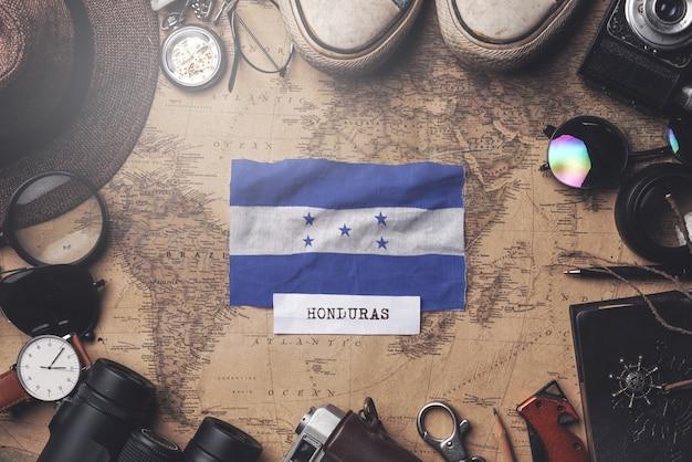 Drapeau du honduras entre les accessoires du voyageur sur l'ancienne carte vintage. tir aérien