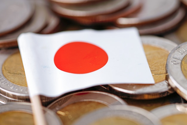 Drapeau du japon sur fond de pièces de monnaie.