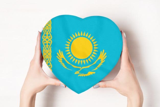 Drapeau du kazakhstan sur une boîte en forme de coeur dans une main féminine. blanc