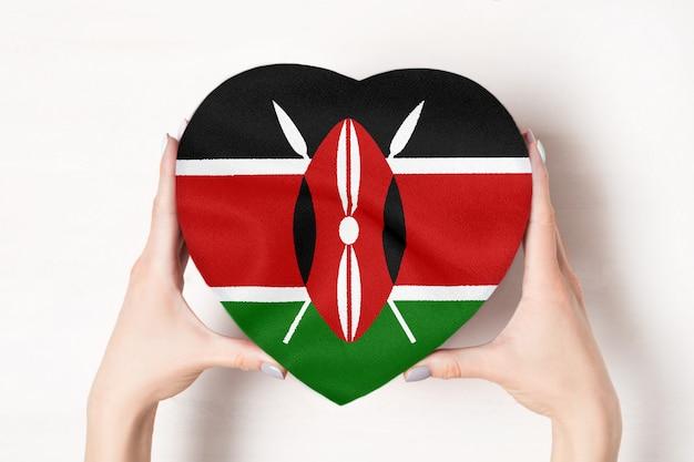 Drapeau du kenya sur une boîte en forme de coeur dans une main féminine.