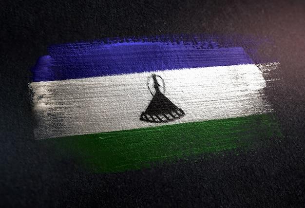 Drapeau du lesotho fait de peinture brosse métallique sur mur sombre grunge