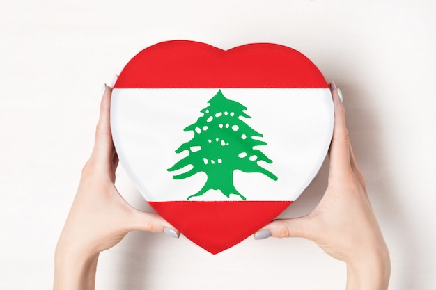 Drapeau du liban sur une boîte en forme de coeur dans une main féminine