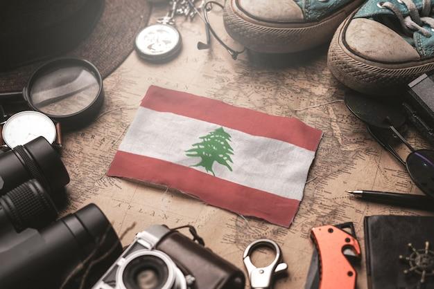 Drapeau du liban entre les accessoires du voyageur sur l'ancienne carte vintage. concept de destination touristique.