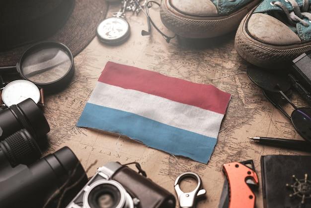 Drapeau du luxembourg entre les accessoires du voyageur sur l'ancienne carte vintage. concept de destination touristique.