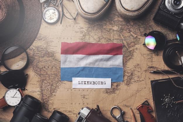 Drapeau du luxembourg entre les accessoires du voyageur sur l'ancienne carte vintage. tir aérien