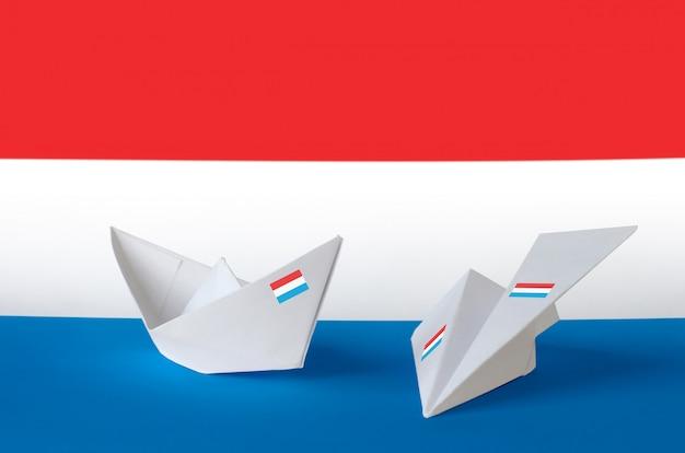 Drapeau du luxembourg représenté sur un avion et un bateau en papier origami. concept d'arts faits à la main