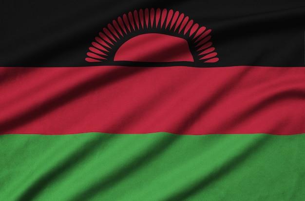Le drapeau du malawi est représenté sur un tissu de sport avec de nombreux plis.