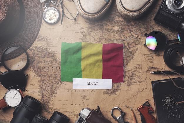 Drapeau du mali entre les accessoires du voyageur sur l'ancienne carte vintage. tir aérien