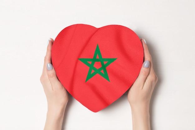 Drapeau du maroc sur une boîte en forme de coeur dans une main féminine