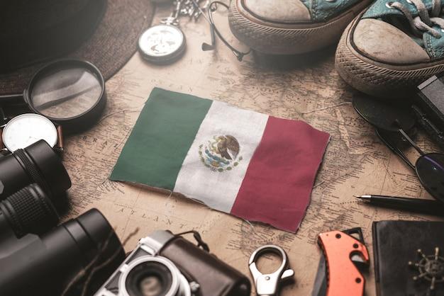 Drapeau du mexique entre les accessoires du voyageur sur l'ancienne carte vintage. concept de destination touristique.