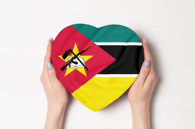 Drapeau du mozambique sur une boîte en forme de coeur dans une main féminine