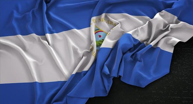 Drapeau du nicaragua enroulé sur un fond sombre 3d render