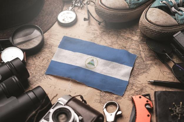 Drapeau du nicaragua entre les accessoires du voyageur sur l'ancienne carte vintage. concept de destination touristique.