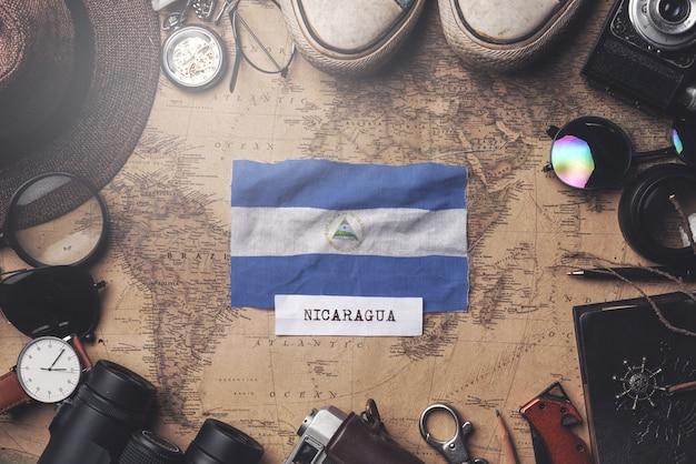 Drapeau du nicaragua entre les accessoires du voyageur sur l'ancienne carte vintage. tir aérien