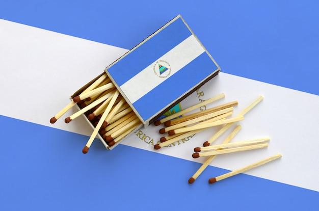 Le drapeau du nicaragua est montré sur une boîte d'allumettes ouverte, à partir de laquelle plusieurs allumettes tombent et repose sur un grand drapeau