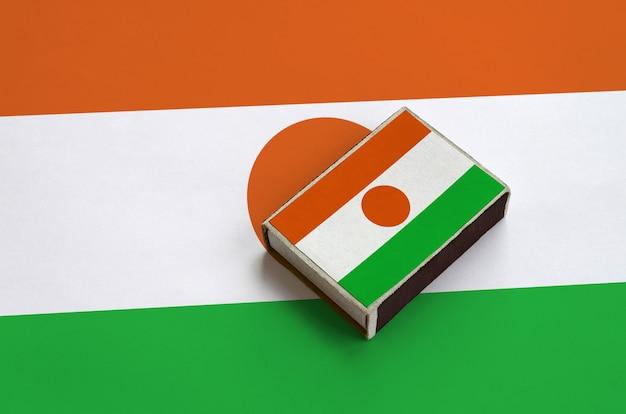 Le drapeau du niger est photographié sur une boîte d'allumettes qui se trouve sur un grand drapeau