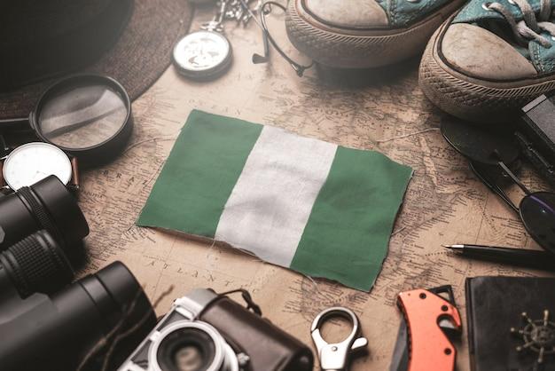 Drapeau du nigeria entre les accessoires du voyageur sur l'ancienne carte vintage. concept de destination touristique.