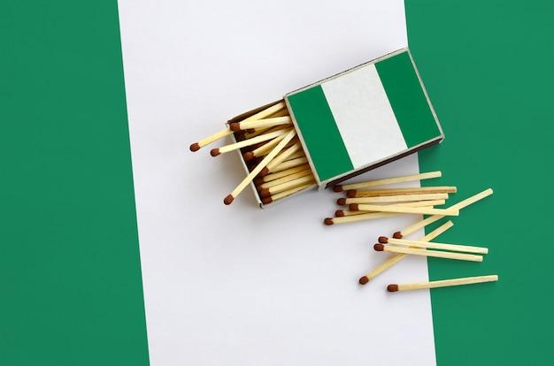 Le drapeau du nigeria est représenté sur une boîte d'allumettes ouverte, à partir de laquelle plusieurs matches tombent et repose sur un grand drapeau