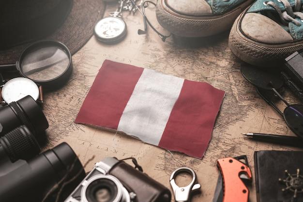 Drapeau du pérou entre les accessoires du voyageur sur l'ancienne carte vintage. concept de destination touristique.