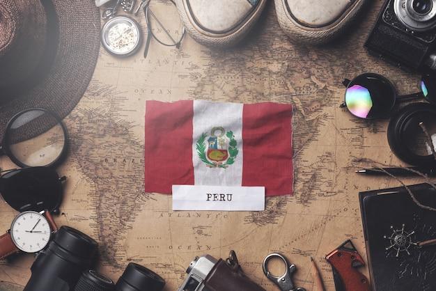 Drapeau du pérou entre les accessoires du voyageur sur l'ancienne carte vintage. tir aérien