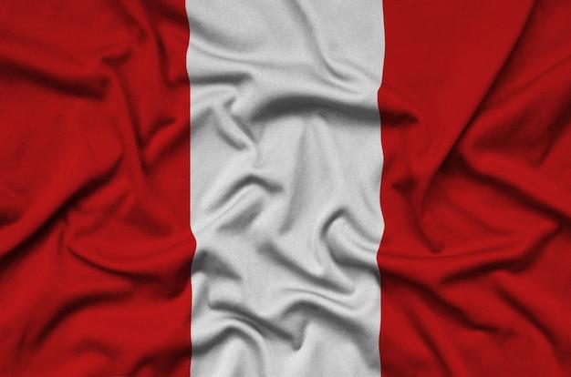 Le drapeau du pérou est représenté sur un tissu de sport avec de nombreux plis.