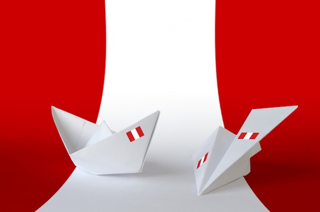 Drapeau du pérou représenté sur un avion et un bateau en papier origami. fond de concept d'arts faits à la main