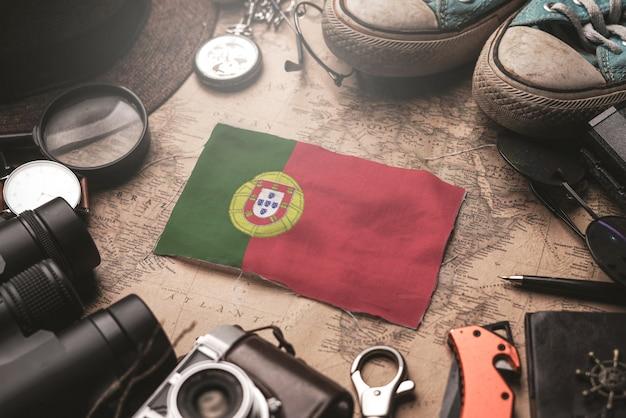 Drapeau du portugal entre les accessoires du voyageur sur l'ancienne carte vintage. concept de destination touristique.