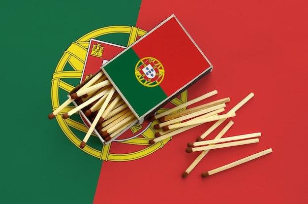 Le drapeau du portugal est montré sur une boîte d'allumettes ouverte, à partir de laquelle plusieurs matches tombent et repose sur un grand drapeau