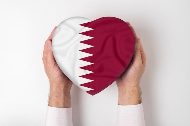 Drapeau du qatar sur une boîte en forme de coeur dans une main masculine.