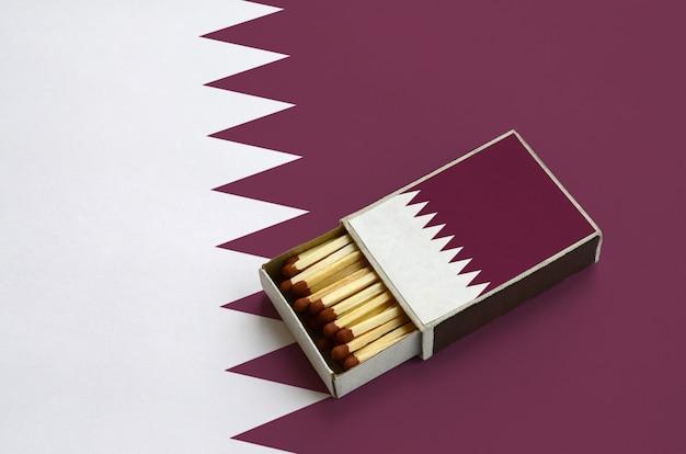 Le drapeau du qatar est montré dans une boîte d'allumettes ouverte, qui est remplie d'allumettes et repose sur un grand drapeau