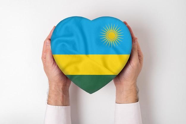 Drapeau du rwanda sur une boîte en forme de coeur dans une main masculine.