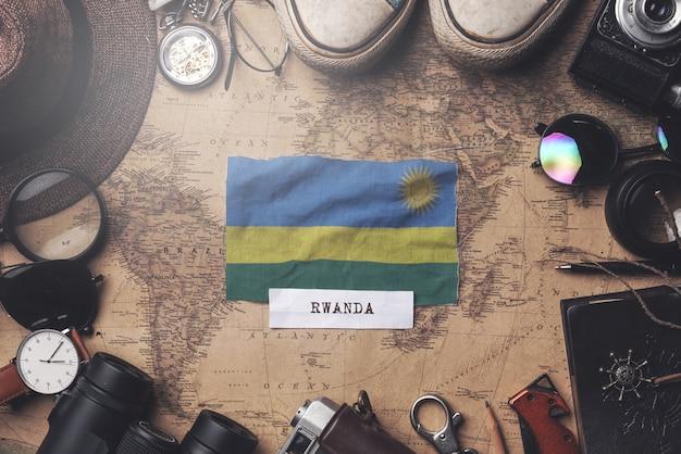 Drapeau du rwanda entre les accessoires du voyageur sur l'ancienne carte vintage. tir aérien
