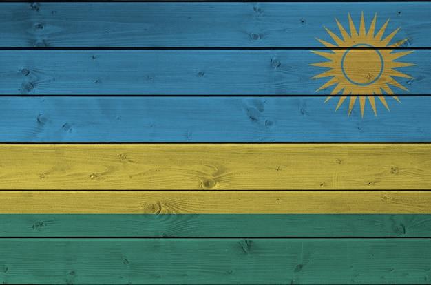 Drapeau du rwanda représenté dans des couleurs vives sur un vieux mur en bois.