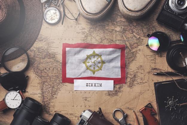 Drapeau du sikkim entre les accessoires du voyageur sur l'ancienne carte vintage. tir aérien