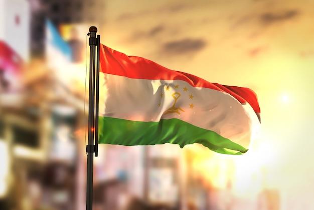 Drapeau du tadjikistan contre la ville contexte flou au sunrise backlight