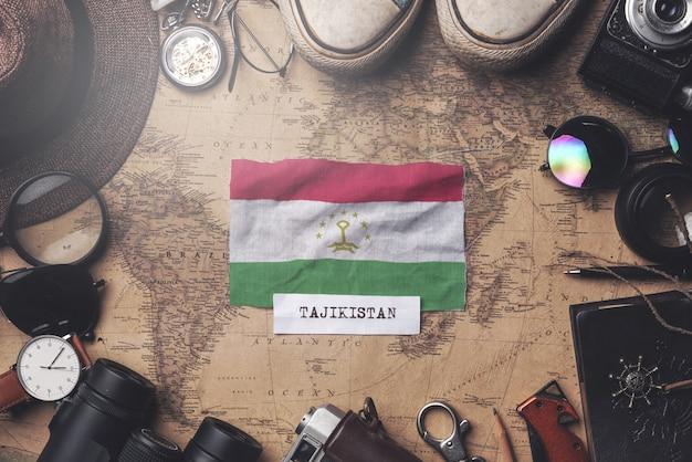 Drapeau du tadjikistan entre les accessoires du voyageur sur l'ancienne carte vintage. tir aérien