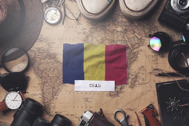 Drapeau du tchad entre les accessoires du voyageur sur l'ancienne carte vintage. tir aérien