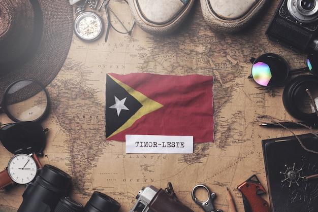 Drapeau du timor oriental entre les accessoires du voyageur sur l'ancienne carte vintage. tir aérien