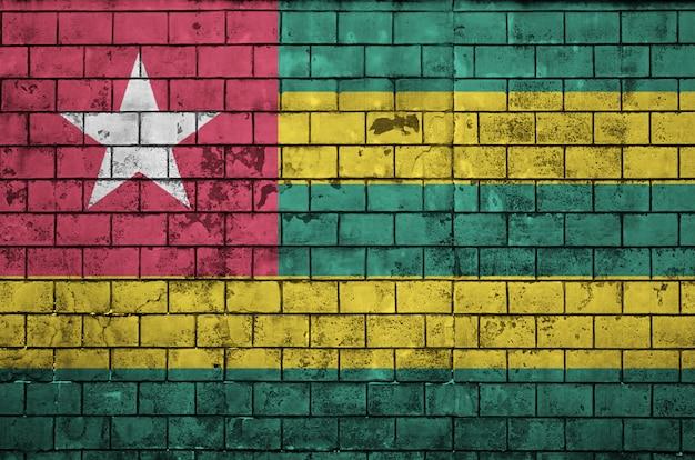Le drapeau du togo est peint sur un vieux mur de briques
