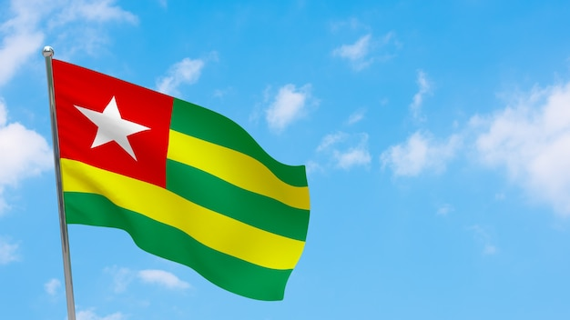 Drapeau du togo sur poteau. ciel bleu. drapeau national du togo