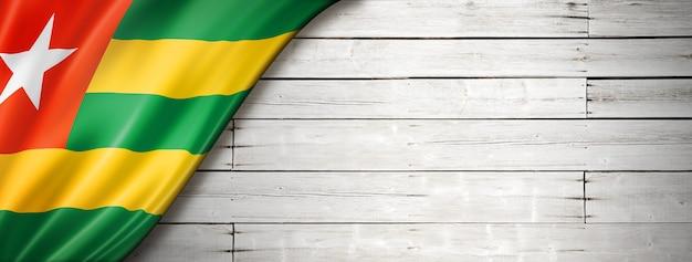 Drapeau du togo sur le vieux mur blanc. bannière panoramique horizontale.