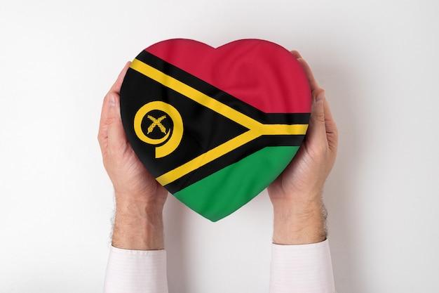 Drapeau du vanuatu sur une boîte en forme de coeur dans une main masculine. fond blanc