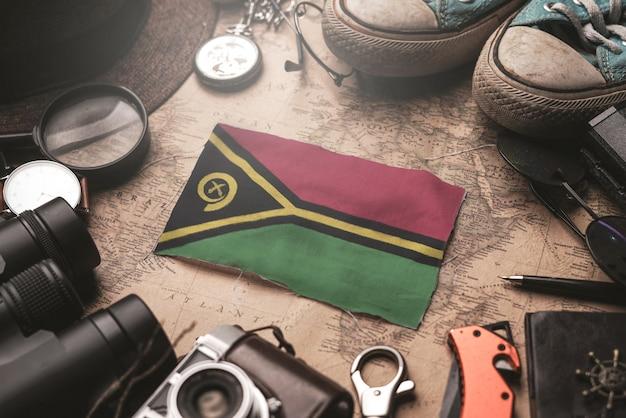 Drapeau du vanuatu entre les accessoires du voyageur sur l'ancienne carte vintage. concept de destination touristique.